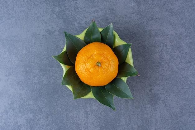 Een enkele sinaasappel met bladeren in een kom, op het donkere oppervlak