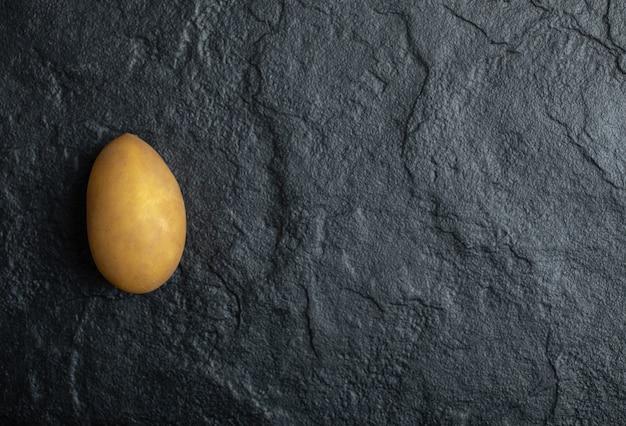 Een enkele verse biologische aardappel op zwarte stenen achtergrond.
