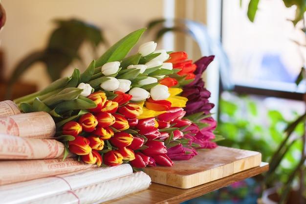 Een enorm veelkleurig boeket tulpen ligt op een tafel in een bloemenwinkel