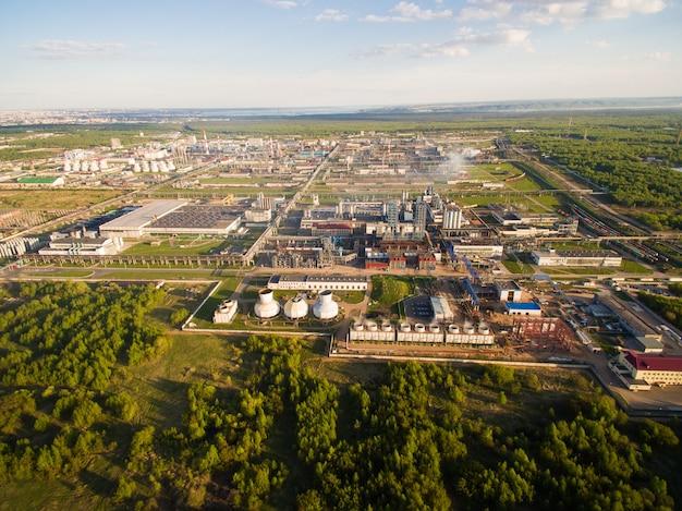 Een enorme olieraffinaderij met pijpen en destillatie van het complex op een groen veld omringd door bos