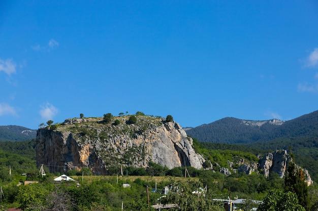 Een enorme rode kalksteenrots, red stone, met bergen op de achtergrond.
