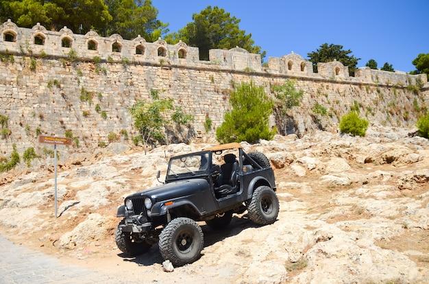Een enorme zwarte jeep in de buurt van het oude fort in rethymno