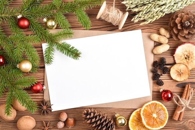 Een envelop en een blanco vel papier op een houten tole met kerstversiering.