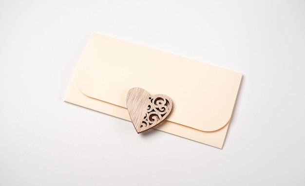 Een envelop en een houten hart erop op wit. liefdesbrief voor valentijnsdag concept.