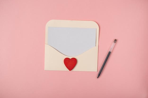 Een envelop met een blanco vel papier erin en een rood hart op de roze achtergrond. romantische liefdesbrief voor valentijnsdag concept.