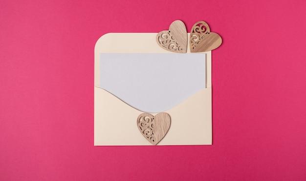 Een envelop met een blanco vel papier erin met drie houten harten op de hete roze achtergrond. valentijnsdag concept. ruimte voor tekst.