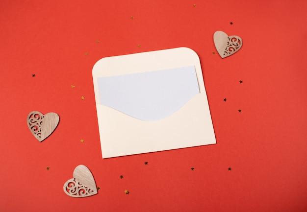 Een envelop met een blanco vel papier erin met drie houten hartjes en sterren op de rode achtergrond. valentijnsdag concept.