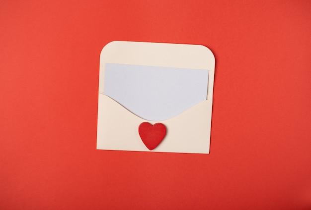 Een envelop met een blanco vel papier erin met een rood hart op de rode achtergrond. valentijnsdag concept.