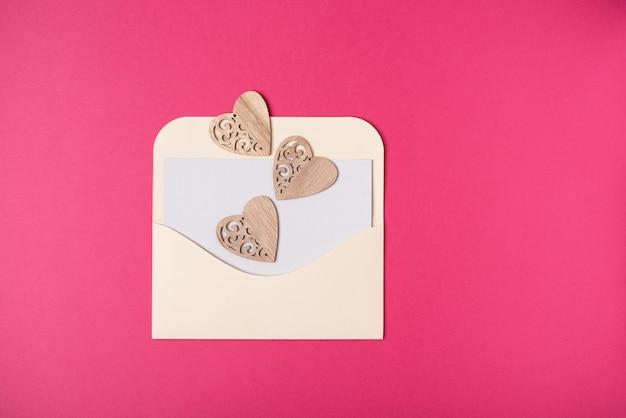 Een envelop met een blanco vel papier erin met hartjes erop op de hete roze achtergrond. valentijnsdag concept. plat lag, bovenaanzicht.