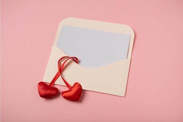 Een envelop met een blanco vel papier erin met rode harten op de roze achtergrond. valentijnsdag concept.