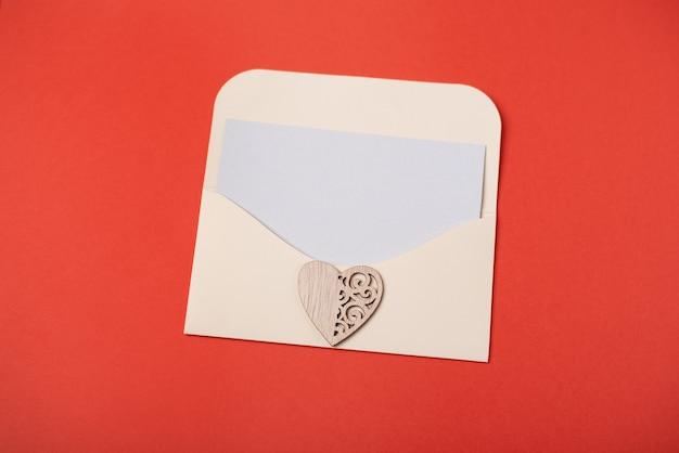 Een envelop met een blanco vel papier met het houten hart op de rode achtergrond. valentijnsdag concept. ruimte voor tekst.