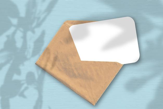 Een envelop met een vel getextureerd wit papier op de zachte blauwe achtergrond. mockup met een overlay van plantschaduwen. natuurlijk licht werpt schaduwen van de boom van geluk. horizontale oriëntatie.