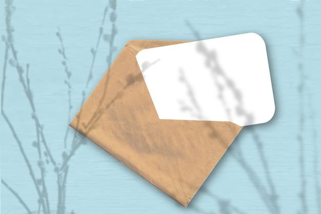 Een envelop met een vel getextureerd wit papier op de zachte blauwe achtergrond. mockup met een overlay van plantschaduwen. natuurlijk licht werpt schaduwen van wilgentakken. horizontale oriëntatie.