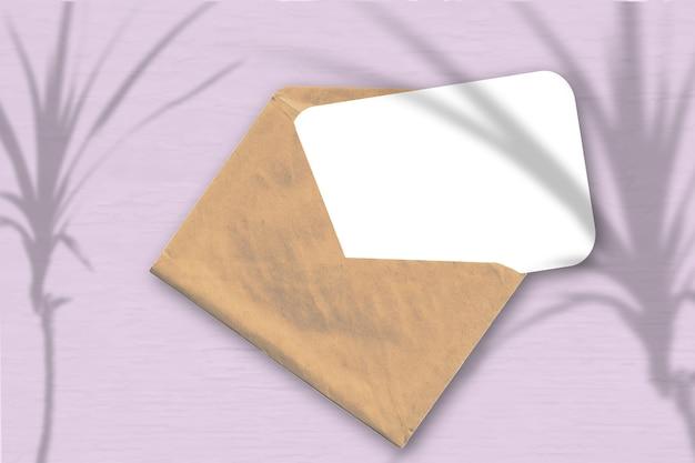 Een envelop met een vel getextureerd wit papier op de zachtroze achtergrond. mockup met een overlay van plantschaduwen. natuurlijk licht werpt schaduwen van een tropische plant. horizontale oriëntatie.