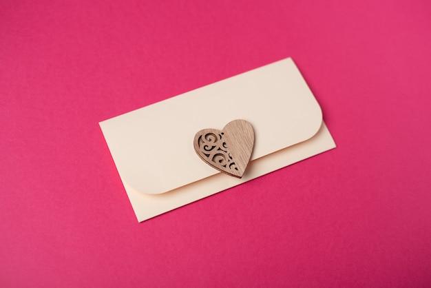 Een envelop met het houten hart op de hete roze achtergrond. valentijnsdag concept.
