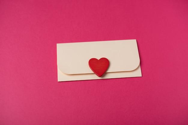 Een envelop met het rode houten hart erop op de hete roze achtergrond. romantische liefdesbrief voor valentijnsdag concept.