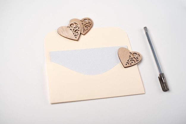 Een envelop met houten hartjes erop en een blanco vel papier binnen op wit. liefdesbrief voor valentijnsdag concept.