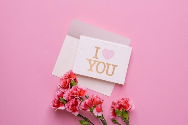 Een envelop met kaart i love you en roze bloemen op roze