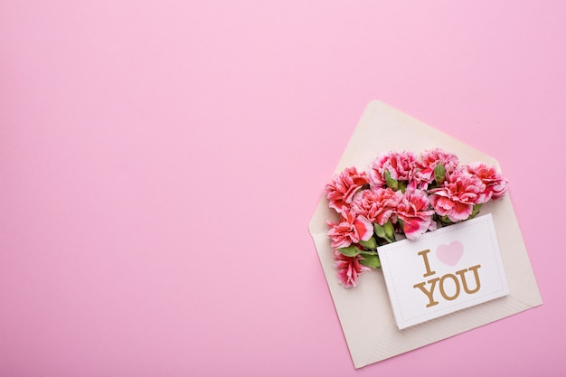 Een envelop met roze bloemen en een kaart i love you on pink