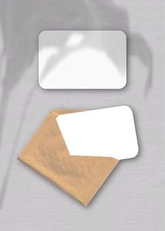 Een envelop met twee vellen gestructureerd wit papier op de grijze achtergrond. mockup-overlay met de plantschaduwen. natuurlijk licht werpt schaduwen van een exotische plant. verticale oriëntatie.