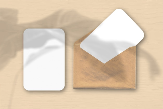 Een envelop met twee vellen gestructureerd wit papier op een gele tafelachtergrond. mockup met een overlay van plantschaduwen. natuurlijk licht werpt schaduwen van een tropische plant. horizontale oriëntatie