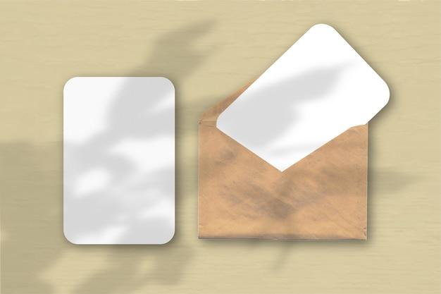 Een envelop met twee vellen gestructureerd wit papier op een gele tafelachtergrond. mockup met een overlay van plantschaduwen. natuurlijk licht werpt schaduwen van een zygocactus. horizontale oriëntatie