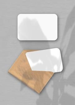 Een envelop met twee vellen getextureerd wit papier op de grijze achtergrond. mockup-overlay met de plantschaduwen. natuurlijk licht werpt schaduwen van de boom van geluk. verticale oriëntatie.