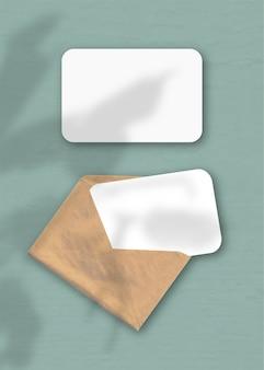 Een envelop met twee vellen getextureerd wit papier op de groene achtergrond van de tafel. mockup-overlay met de plantschaduwen. natuurlijk licht werpt schaduwen van een exotische plant