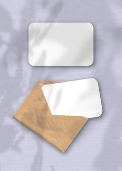 Een envelop met twee vellen getextureerd wit papier op de paarse achtergrond van de tafel. mockup-overlay met de plantschaduwen. natuurlijk licht werpt schaduwen van de boom van geluk.