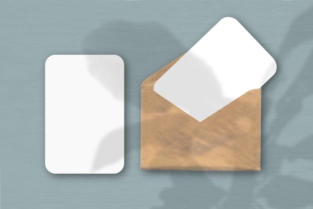 Een envelop met twee vellen getextureerd wit papier op een grijze tafelachtergrond. mockup met een overlay van plantschaduwen. natuurlijk licht werpt schaduwen van de boom van geluk.