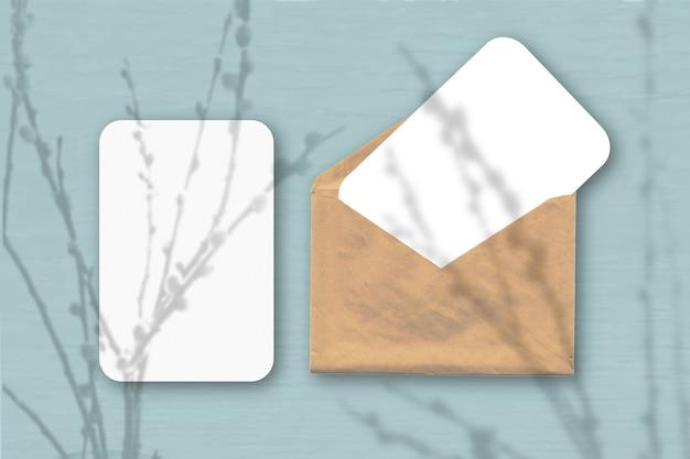 Een envelop met twee vellen getextureerd wit papier op een grijze tafelachtergrond. mockup met een overlay van plantschaduwen. natuurlijk licht werpt schaduwen van wilgentakken. horizontale oriëntatie