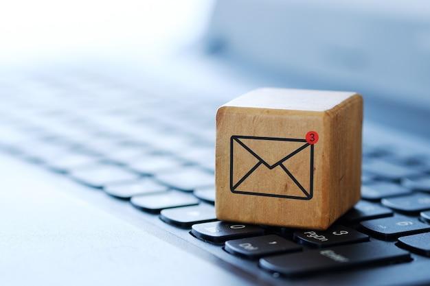 Een envelopsymbool op een houten kubus op een computertoetsenbord, met een vage achtergrond en ondiepe scherptediepte.