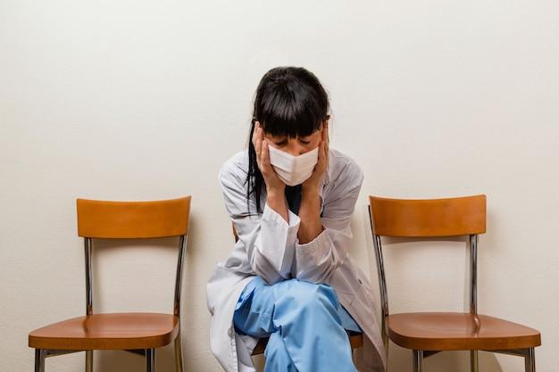 Een erg vermoeide, huilende en peinzende verpleegster die na haar dienst in het ziekenhuis in een wachtkamer zit.