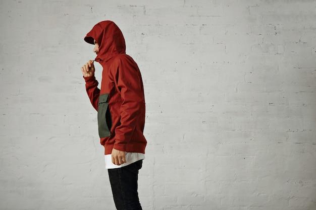 Een ernstig uitziende jongeman ritst zijn rode en grijze anorak dicht, portret vanaf de zijkant geïsoleerd op wit