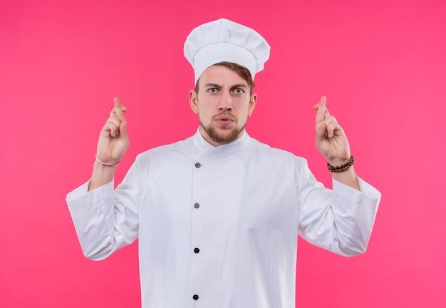 Een ernstige jonge, bebaarde chef-kokmens in wit uniform kruist middelvinger over wijsvinger op een roze muur