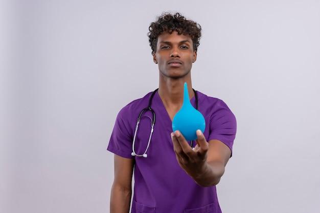 Een ernstige jonge knappe donkere arts met krullend haar die violet uniform draagt met een stethoscoop die een klysma toont