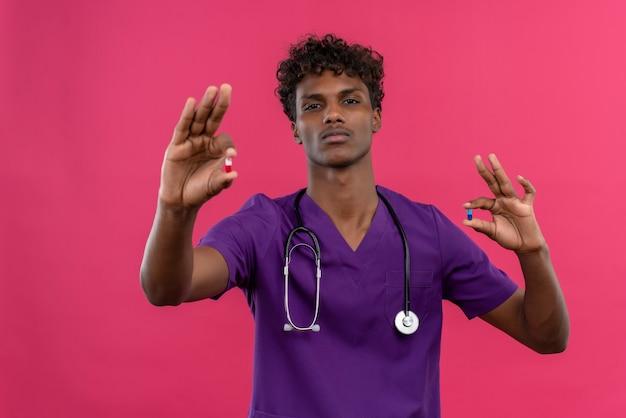 Een ernstige jonge knappe donkere arts met krullend haar die violet uniform draagt met een stethoscoop die pillen toont