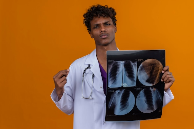 Een ernstige jonge knappe donkere mannelijke arts met krullend haar die witte laag met stethoscoop draagt die röntgenrapport toont