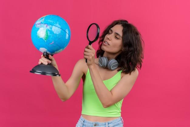 Een ernstige jonge mooie vrouw met kort haar in groene crop top in koptelefoon kijken globe gestaag met vergrootglas