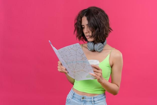 Een ernstige jonge mooie vrouw met kort haar in groene crop top in koptelefoon met plastic kopje koffie kijken naar kaart