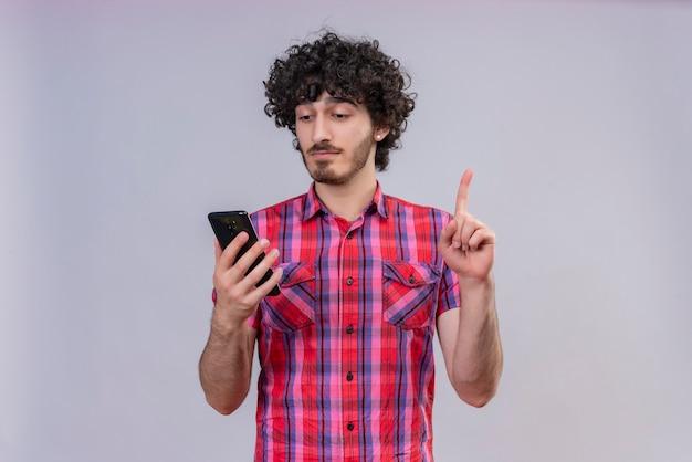 Een ernstige jongeman met krullend haar in een geruit overhemd die met wijsvinger wijst en naar mobiele telefoon kijkt