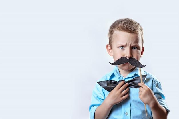 Een ernstige jongen fronsen in een licht shirt zet een snor op een stok en een strik op zijn gezicht om hem ouder te laten lijken.