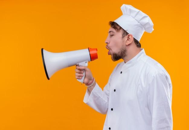 Een ernstige knappe jonge bebaarde chef-kok man in wit uniform spreken via megafoon op een oranje muur
