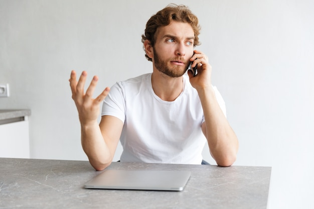 Een ernstige verwarde jonge bebaarde man aan de tafel thuis praten via de telefoon in de buurt van laptop computer.