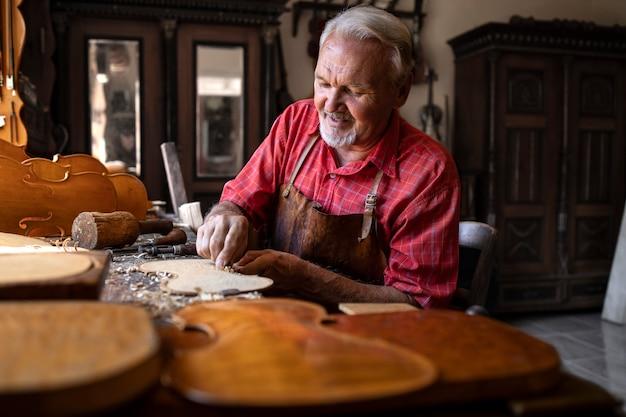 Een ervaren senior timmerman met grijs haar die aan zijn project in een timmerwerkplaats werkt