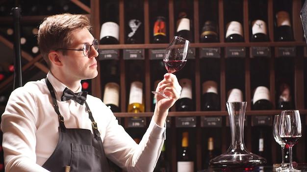 Een ervaren sommelier kijkt naar de wijn in het glas. wijnproeverij in een wijnboetiek, close-up