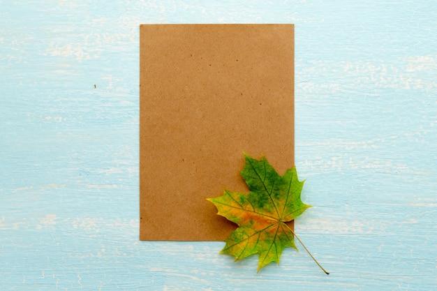 Een esdoornblad in de buurt van een blanco vel papier. frame voor tekst, herfstthema. uitzicht van boven.