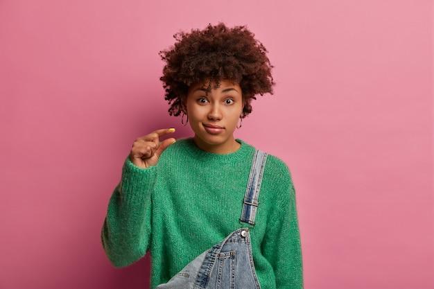 Een etnische vrouw met een donkere huidskleur en een donkere huidskleur vertoont iets heel kleins, kleine of minuscule vormen