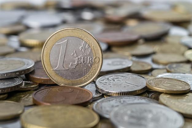 Een euromunt tegen het oppervlak van andere verschillende munten