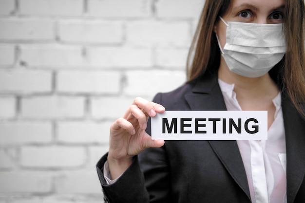Een europees meisje dat een medisch masker draagt, houdt een bordje vast met het opschrift meeting